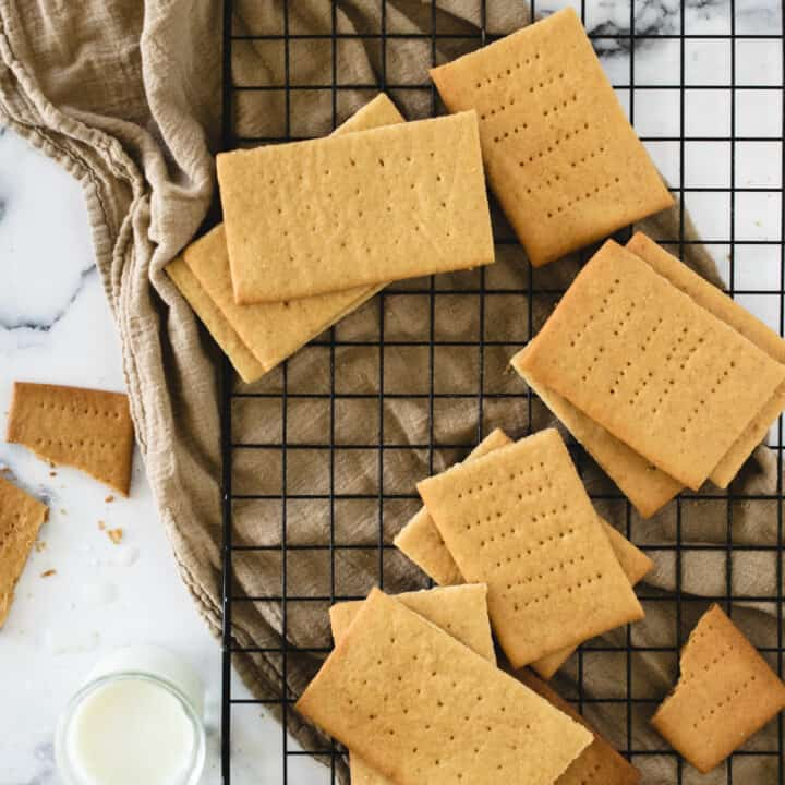 graham crackers on cooling rack next to glass of milk an crumbs
