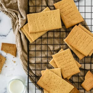 Graham crackers on a baking rack next to a glass of milk.