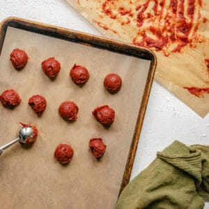 Scooping tomato paste onto a baking sheet.