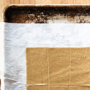 slab of brown dough cut and trimmed into rectangles with holes poked in them on a baking sheet
