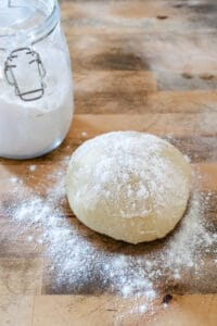 Dough ball dusted with flour on wooden surface.