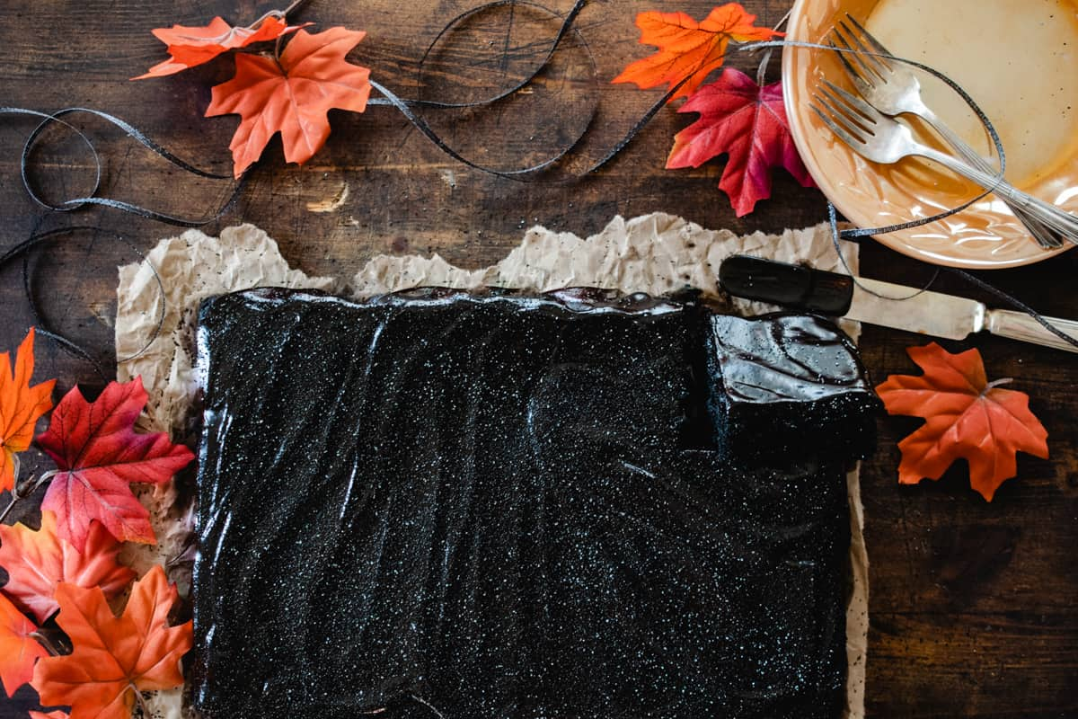 Black chocolate sheet cake with metallic sprinkles, Fall leaves, and black ribbon.