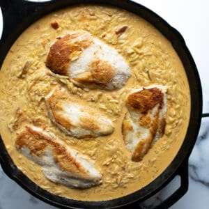 A skillet with chicken breast and orzo in a creamy sauce.
