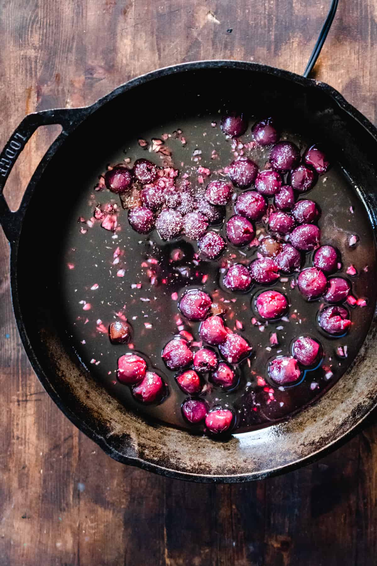 Cast iron skillet with cherries, wine and herbs.