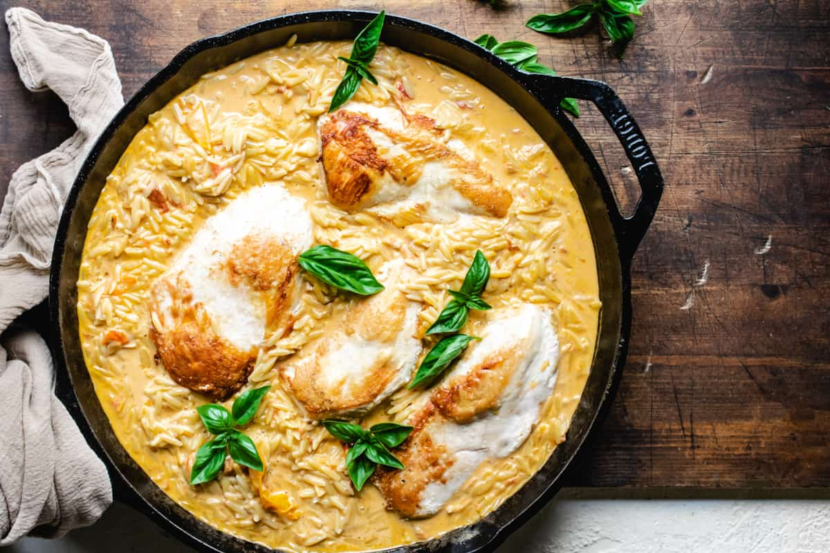 Cast iron skillet with creamy orzo, four chicken breasts, and fresh basil leaves on wooden cutting board.