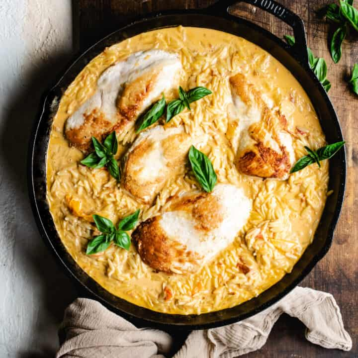 Cast iron skillet with taupe towel filled with orzo in a yellow, creamy sauce, topped with chicken breast.