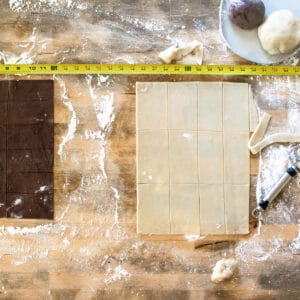 White and chocolate dough cut into rectangles on floured wooden surface with measuring tape along side.