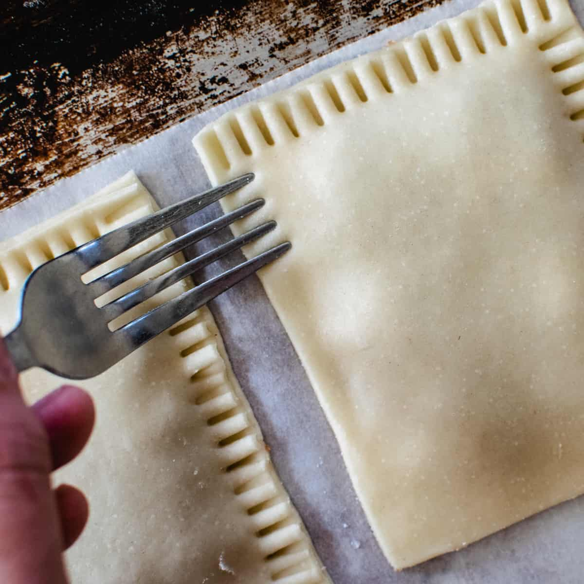 Homemade pop tarts being pressed with the tines of a fork to seal.