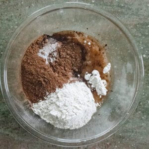 Glass bowl with flour, cocoa powder, oil and eggs.