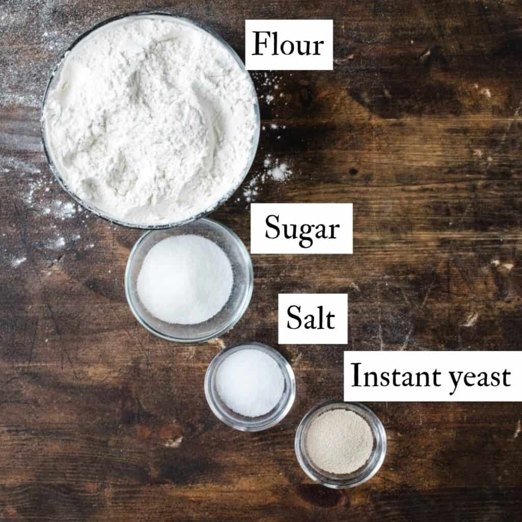 Bowls of flour, sugar, salt and yeast with text labels.