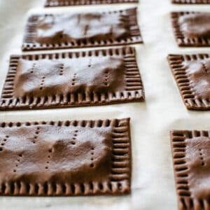 Uncooked chocolate pop tarts with holes poked in them.