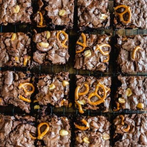 Pretzel and peanut brownies cut into squares on a cooling rack.