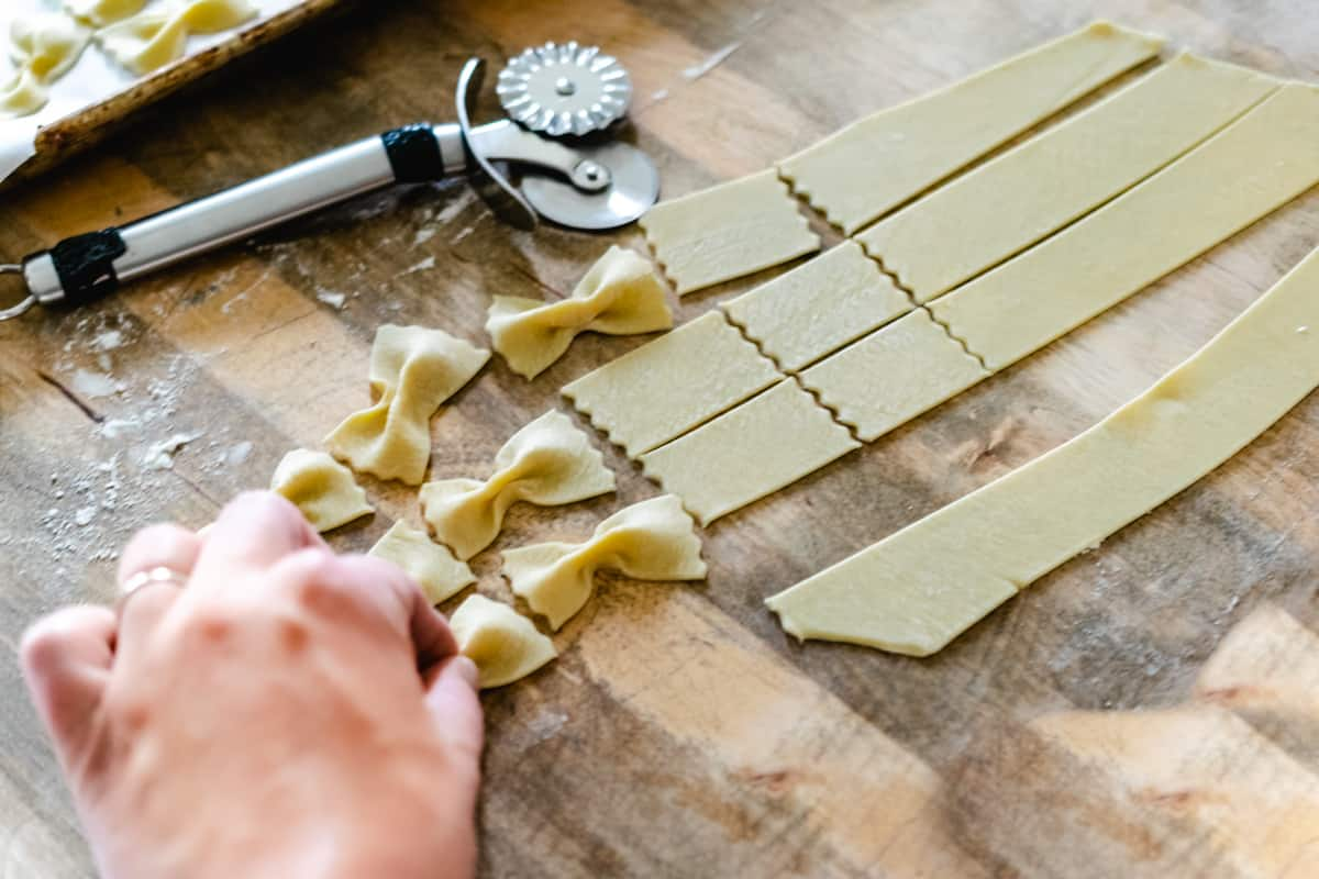 Pinching pasta shapes together to form bowtie pasta by hand.