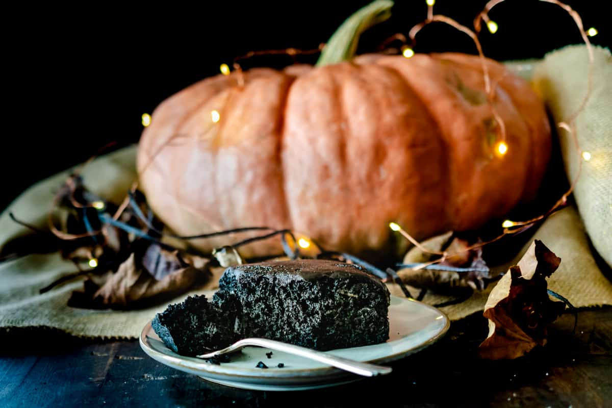 Chocolate cake with a bite taken out in front of decorative lights and pumpkin on a piece of burlap.