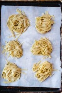 Six nests of fresh fettuccine pasta on a baking sheet.