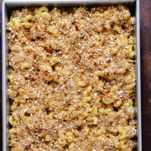 Cheesy macaroni pasta covered in breadcrumbs in a metal casserole dish.