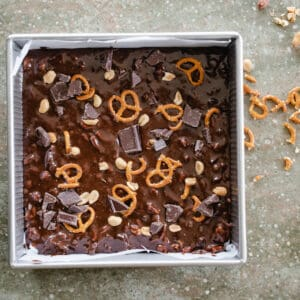 Square metal pan with brownie batter topped with pieces of chocolate, peanuts and pretzels.