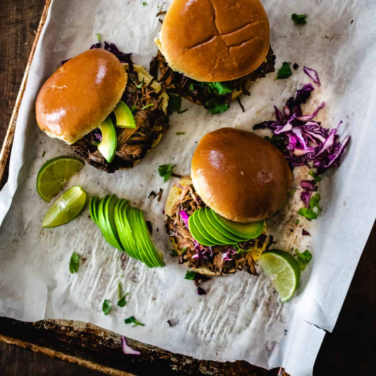 Three shredded beef sandwiches topped with avocado and lime.