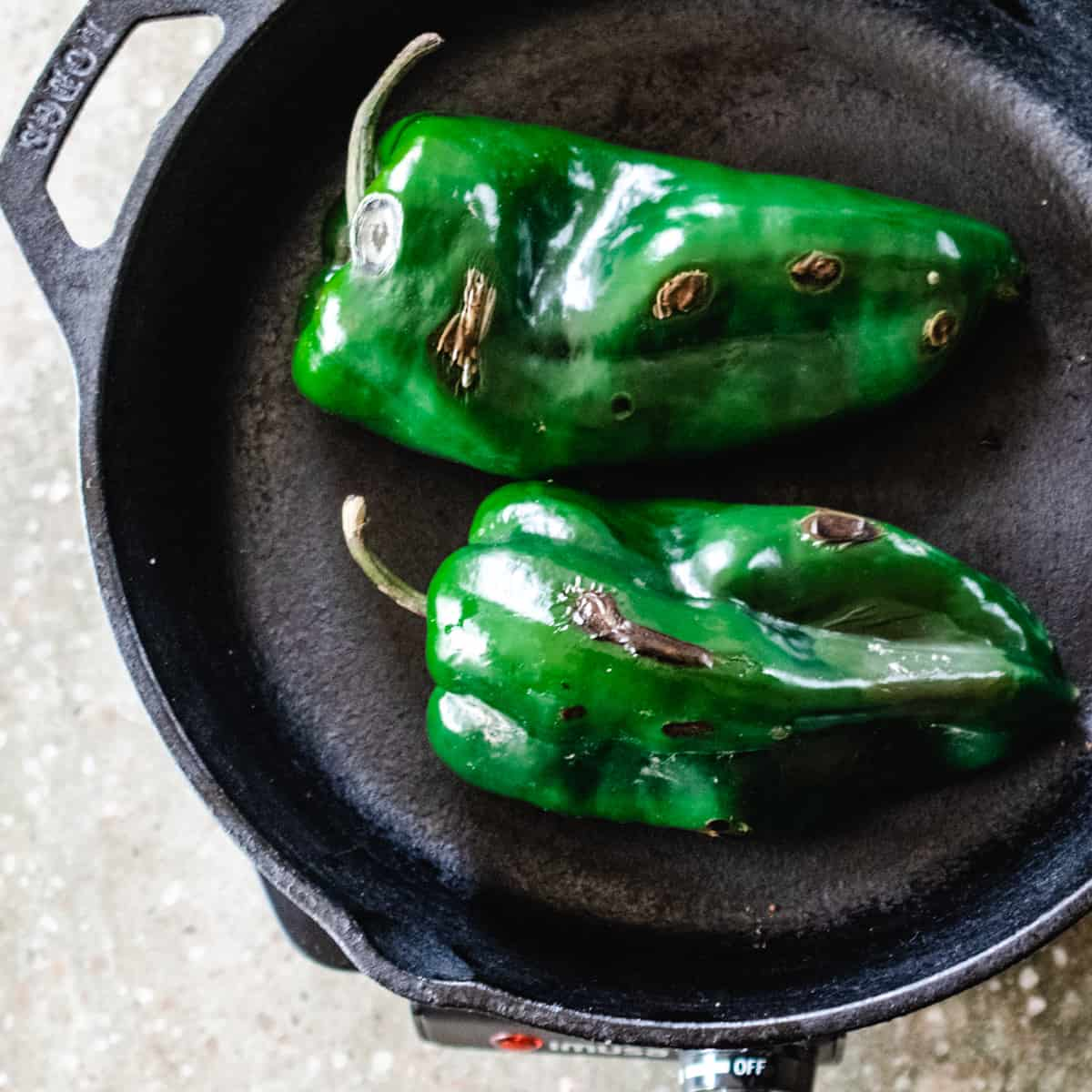Two poblano peppers in a cast iron skillet being blistered.