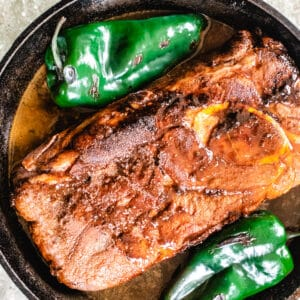 Seared beef in a deep skillet with poblano peppers and beer.