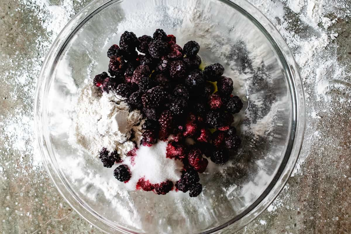 Blackberries and raspberries in a bowl with flour, sugar and melted butter.