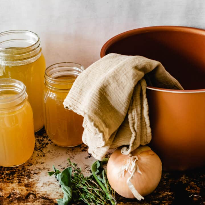 Instant Pot inner pot by jars of bone broth and vegetables.