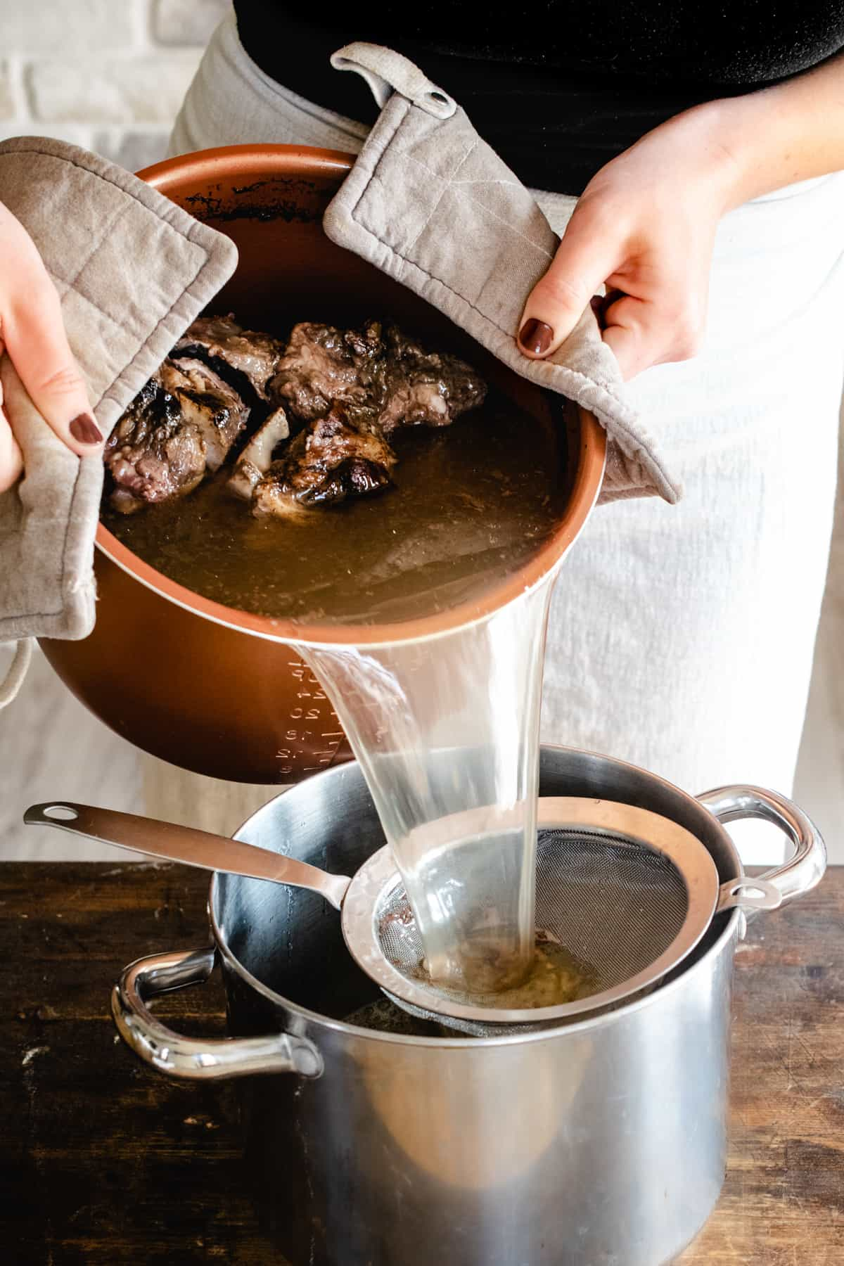 Pouring beef bone broth through a mesh strainer.