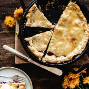 Pie with two slices cut out surrounded by orange flowers on wooden cutting board.