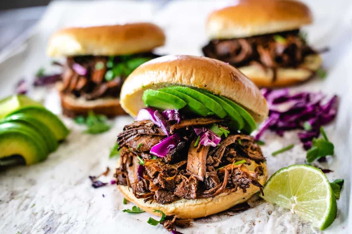 Shredded beef on a hamburger bun with avocado, lime, cilantro and cabbage.