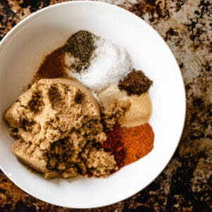 Spices and brown sugar in a white bowl.