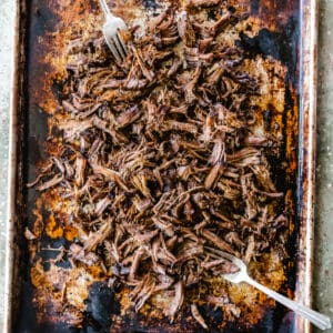 Shredded beef on a baking sheet being pulled apart with two forks.