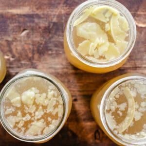 Bone broth in jars with solid fat pieces on top layer.