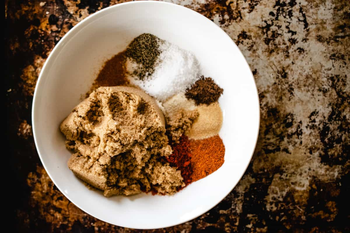 White bowl filled with dried spices and brown sugar.
