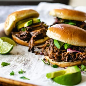 Pulled beef sandwiches with avocado, cilantro, cabbage and lime wedges.