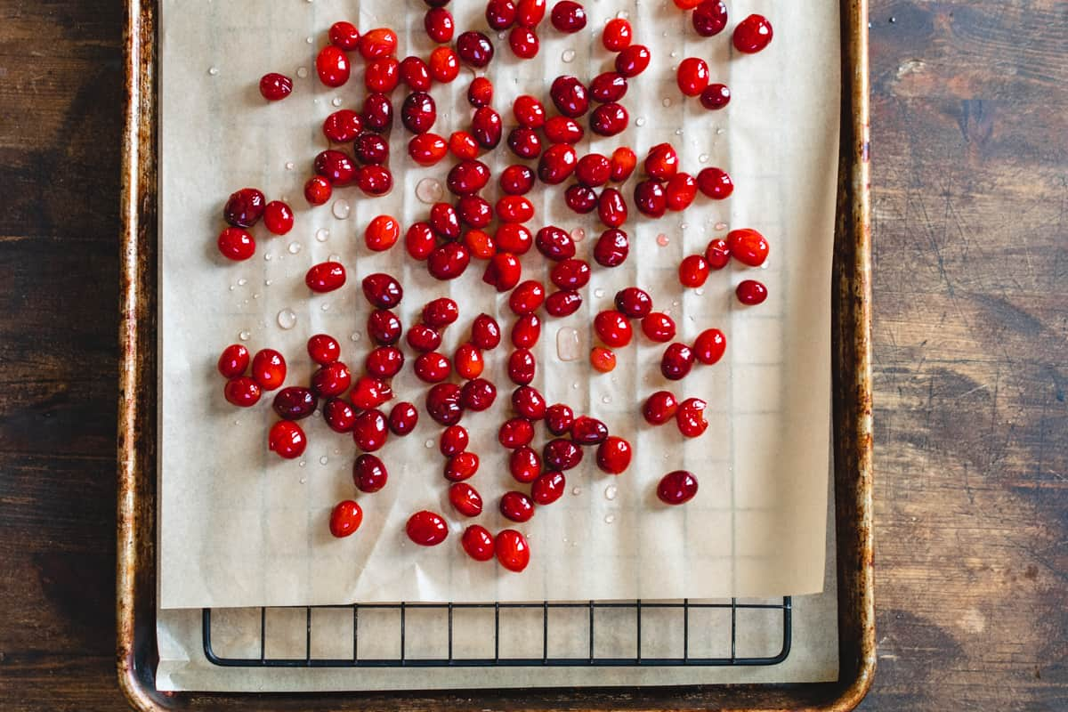 Whole cranberries covered in sugar water on parchment paper lined baking sheet.