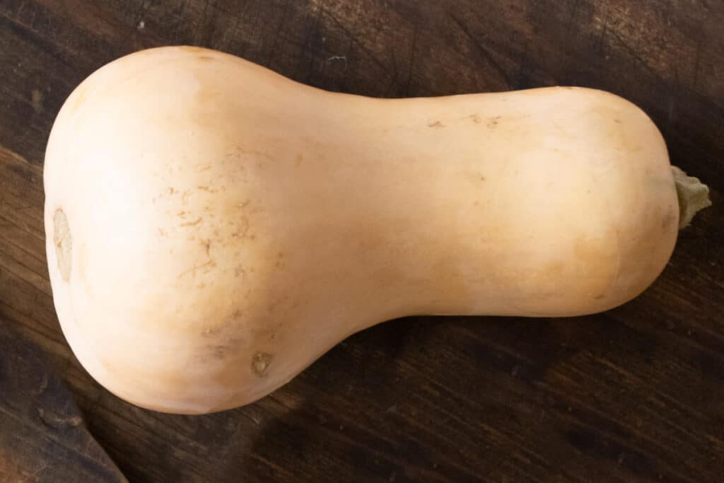 A butternut squash on a wooden surface.