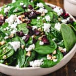 A salad bowl of spinach leaves, goat cheese, walnuts and cranberries next to bowl of dressing.