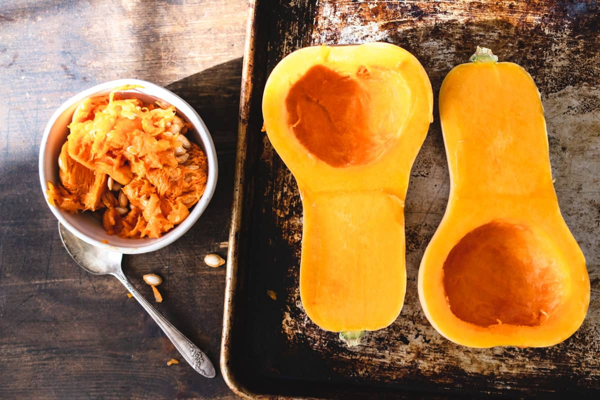 Two butternut squash halves on a baking sheet next to bowl of seeds and pulp.