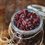 A jar of dried cranberries on wo