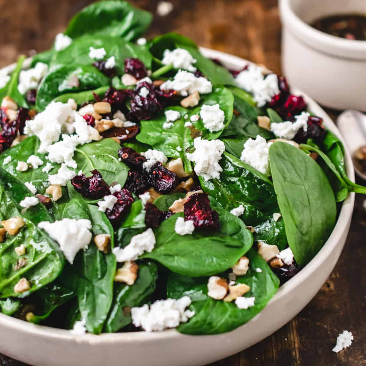Salad bowl of baby spinach, goat cheese crumbles, dried cranberries, and walnuts with bowl of dressing.