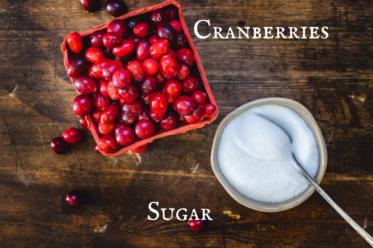 Fresh cranberries in a red fruit box by a bowl of sugar with a spoon.