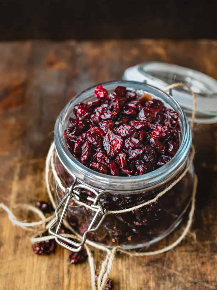 Glass jar of dried cranberries on wooden table.