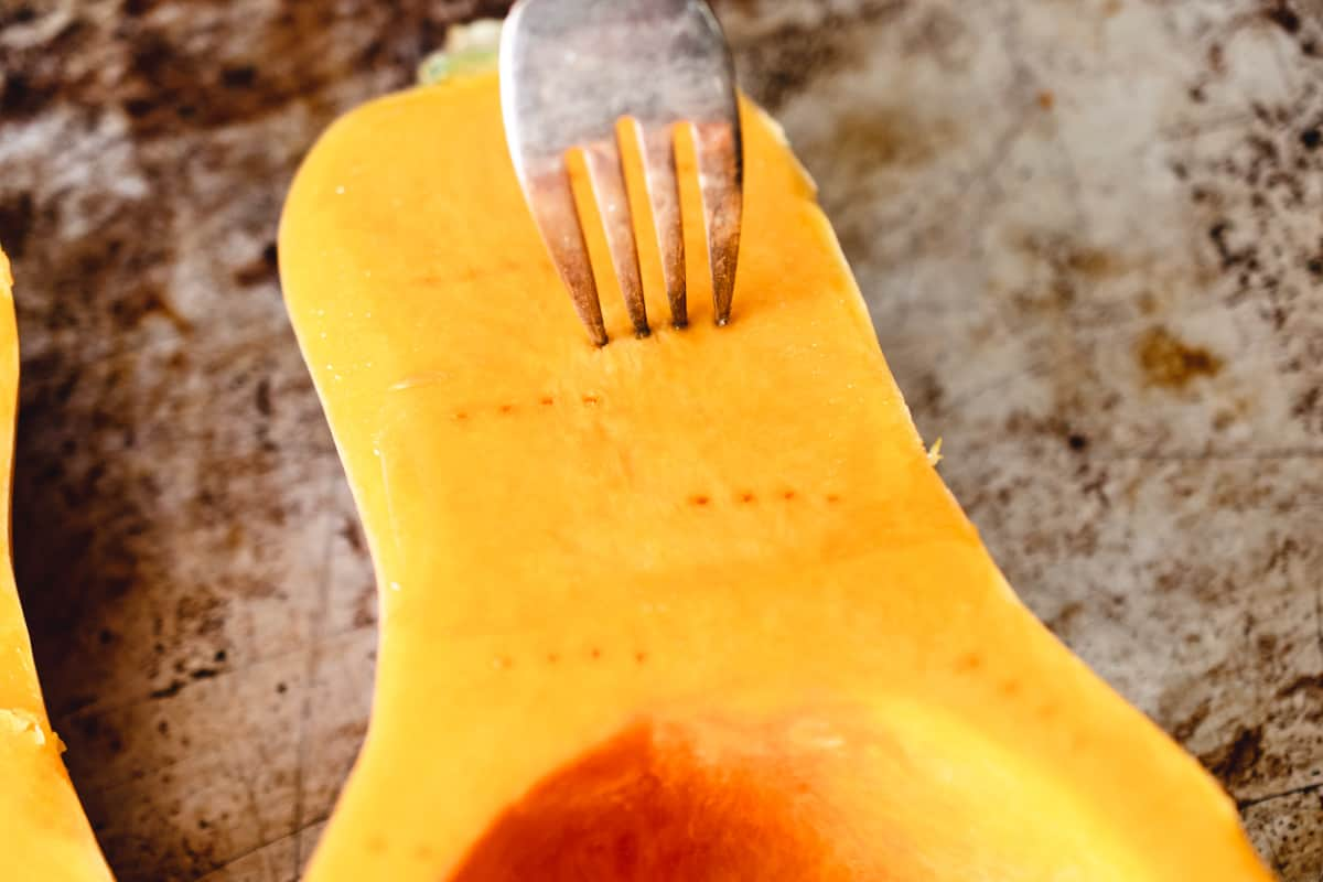 A fork poking holes in to a cut butternut squash.