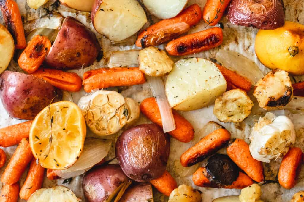 Roasted carrots, potatoes, garlic and parsnips on a baking sheet.