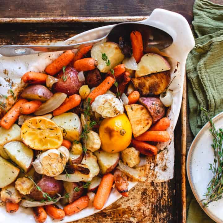 Roasted root vegetables in a baking dish with large serving spoon.