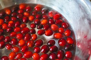 Cranberries with splits in them floating in water in a metal bowl.