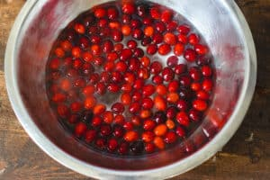 Stainless steel bowl filled with cranberries and water.