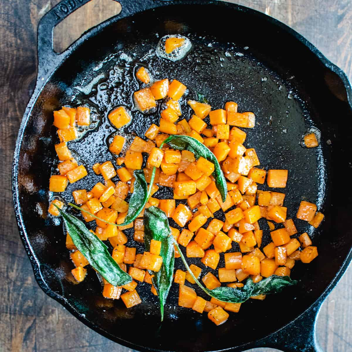 Diced sweet potato and sage being fried in a skillet