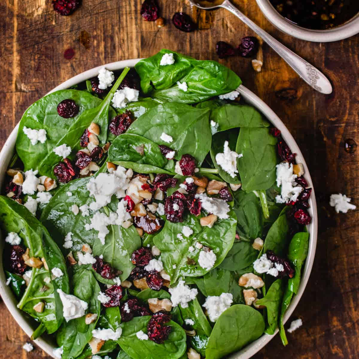 Spinach leaves, dried cranberries, walnut pieces and crumbled cheese in a bowl on wooden backdrop.