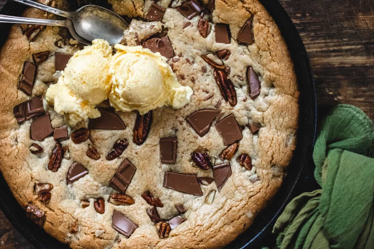 Cookie in a cast iron skillet with chunks of chocolate and pecans.